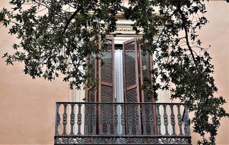 Balcon de maison avec des volets mi-clos