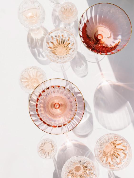 Verres en cristal contenant un liquide rose nimbés de lumières