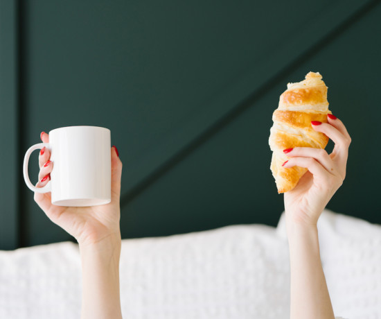 mains de femmes dans un lit tenant un mug blanc et un croissant