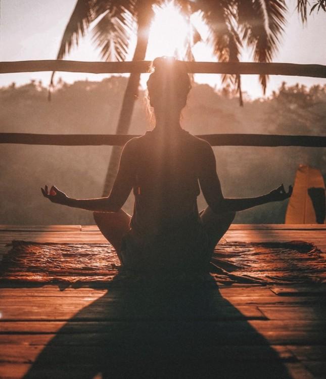 Femme en position du lotus au coucher du soleil
